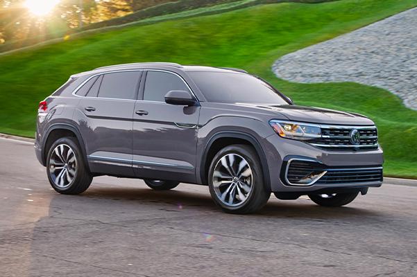 The Atlas Cross Sport drivesalongside a well-manicured lawn filled with gray cobblestones.