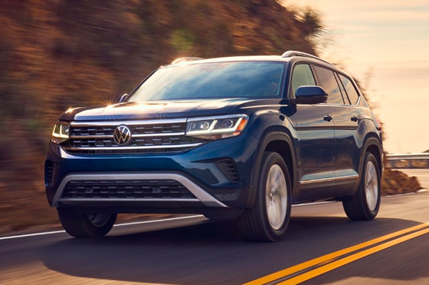Front shot of the Atlas shown in Tourmaline Blue Metallic driving on the road at sunset.